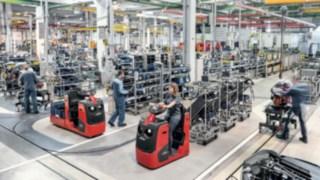 Dragtruck med flera varuvagnar transporterar komponenter till tillverkningslinan.