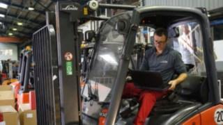 Tekniker med laptop som inspekterar en truck som förbereds för renovering